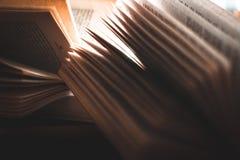 Een stapel van open pocketboeken achter aangestoken door vensterlicht stock foto