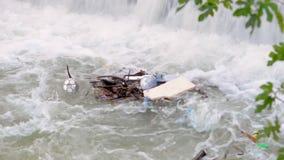 Een stapel van puin in de rivier onder de gateways aan de stad stock video