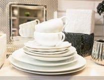 Een stapel van schoon leeg wit porseleinvaatwerk op een plank Keukengerei binnen de opslag of thuis stock foto