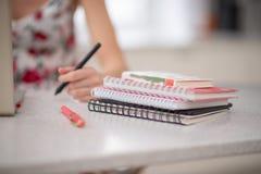 Een stapel van spiraalvormige notitieboekjes en studente bij laptop stock fotografie
