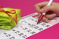 Een stapel van stootkussens en een meisje omringt de dagen op de kalender met een rode viltpen wanneer zij haar menstruatie, clos royalty-vrije stock afbeelding