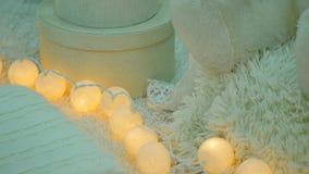 Een stapel witte en beige hoofdkussens en dekens met koordlichten op uitstekende houten stoel Comfortabele binnenlandse zachte de stock footage