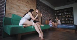 In een stedelijke groep van de ontwerpzitslaapkamer van vier vriendendames die in pyjama's van de ochtend genieten die samen babb stock footage