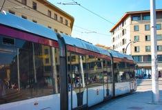 Een stedelijke tramlooppas door de chaos van stadsstraten om forenzen aan hun bestemming te brengen stock afbeelding