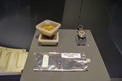 Een steekproef van voedselastronauten eet terwijl zij in ruimte met abrikozendrank en een ruimtehorloge zijn stock afbeeldingen