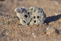 Een steen die op een kaas lijken ligt op het zand en lijkt op een berg royalty-vrije stock foto's