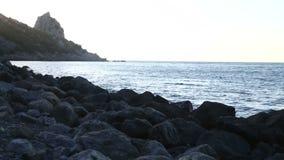 Een steenachtige overzeese kust tegen de achtergrond van de avondhemel Statische camera stock videobeelden