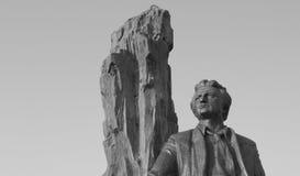 Een steenstandbeeld van een mens tegen een witte hemel Stock Afbeelding