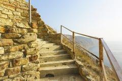 Een steentrap op een steile berghelling boven het overzees Stock Foto's