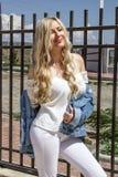 Een stelt de mooie jonge blonde vrouwenglimlachen, tribunes door de omheining, en prachtig royalty-vrije stock afbeeldingen