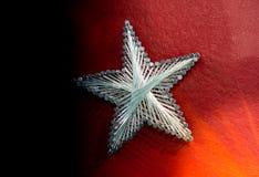 Een ster maakte van staalspijkers en koord op rode achtergrond royalty-vrije stock afbeeldingen