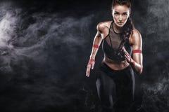 Een sterke atletische, vrouwensprinter, die op zwarte achtergrond lopen die in de sportkleding, de fitness en de sportmotivatie d
