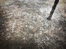 Een stevig, hard de boorbeetje van het metaalijzer boort een gat in een grote grijze steen Dichte Mening De achtergrond royalty-vrije stock foto's