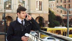 Een stevige mens bevindt zich op de straat en spreekt op de telefoon stock video