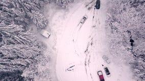 Een stijgend luchtschot van een sneeuwparkeerterrein en een sneeuw behandelde bomen in de bergen stock videobeelden