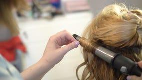 Een stilist maakt tot een kapsel aan een vrouw die haar haar krullen die omhoog close-up krullen stock videobeelden
