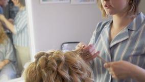 Een stilist maakt tot een kapsel aan een vrouw die haar haar krullen die omhoog close-up krullen stock footage