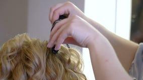 Een stilist maakt tot een kapsel aan een vrouw die haar haar krullen die omhoog close-up krullen stock video