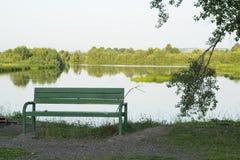 Een stille plaats met een bank bij de rivier Stock Afbeeldingen