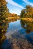 Een stille vermoeide rivier vloeit door de herfst zonnig bos 2 stock afbeeldingen