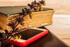 Een stilleven van een oud boek, een modern apparaat en een bloeiende bar stock afbeelding
