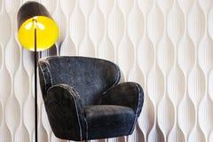 Een stoel en een gloeiende schaduw tegen de witte gevormde muur royalty-vrije stock foto's