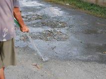 Een stoffige weg die verhinderend het stof dat omhoog door voertuigen water worden gegeven moet worden geschopt die over de landw stock fotografie
