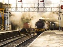 Een stoomtrein die een post` s platform met golvende rook ingaan stock afbeelding