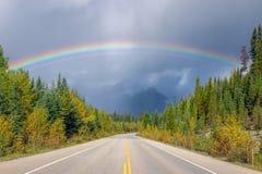Een stormachtige hemel en een regenboog over lege asfaltweg 93 alberta canada royalty-vrije stock afbeeldingen