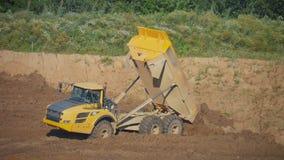 Een stortplaatsvrachtwagen maakt de grond van de carrosserie leeg stock video
