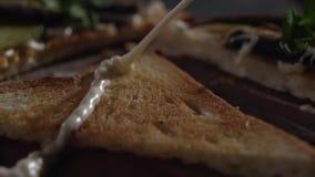 Een straal van saus valt op de toost stock video