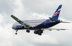 Een straalpassagiersvliegtuig in een blauwe hemel Stock Afbeelding