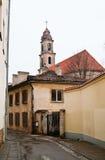 Een straat van Vilnius en de oude kerk Stock Afbeeldingen