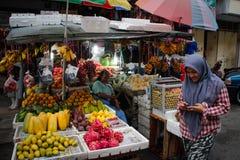 Een straatmarkt in het kapitaal met dienbladen van exotische vruchten en kopers stock foto's