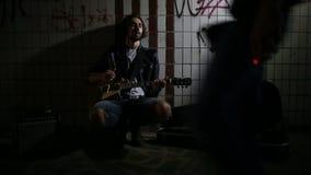 Een straatmusicus die op gitaar in de onderdoorgang spelen Zwerverlevensstijl Het spelen in de onderdoorgang om het leven te make stock videobeelden