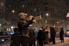 Een straatmusicus speelt trompet in de hoofdstraat van de stad a stock afbeelding