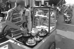 Een straatventer bereidt te verkopen cake voor Stock Foto's