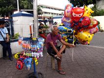 Een straatventer verkoopt bellenmakers en de ballons van het beeldverhaalkarakter bij een park stock foto's