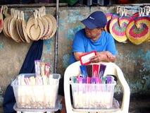 Een straatventer verkoopt een verscheidenheid van kleurrijke handventilators stock afbeelding