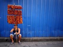 Een straatventer verkoopt kleurrijke slingers van droge Eeuwige bloemen stock foto