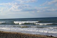 Een strand met golven die binnen op een bewolkte dag komen stock afbeeldingen