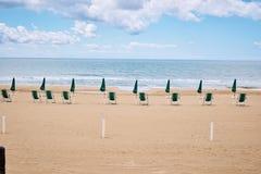 Een strand met paraplu's en zonbedden op kust stock afbeeldingen