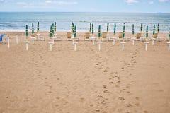 Een strand met paraplu's en zonbedden op kust stock afbeelding