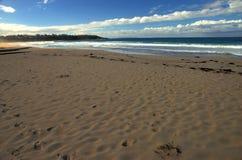 Een strand in schaduw stock afbeeldingen