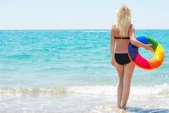 Een strandvakantie De mooie sexy vrouw in bikini met opblaasbare cirkel kijkt uit aan overzees royalty-vrije stock fotografie