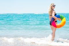 Een strandvakantie De mooie sexy vrouw in bikini met opblaasbare cirkel kijkt uit aan overzees stock foto's