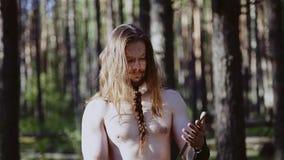Een strijder met lang haar en een naakt torso onderzoekt de bezinning in een groot blad Viking bekijkt zijn wapen stock footage