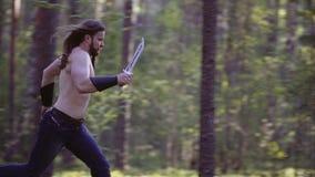 Een strijder met een naakt torso en een koud wapen in handen die, snel het hout doornemen die iemand achtervolgen Kader in langza stock footage