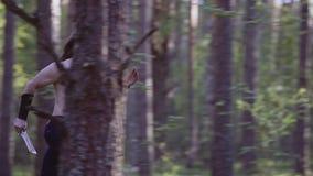 Een strijder met een naakt torso en een koud wapen in handen die, snel het hout doornemen die iemand achtervolgen Kader in langza stock videobeelden