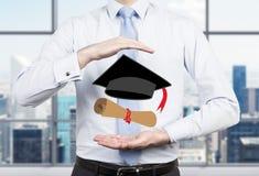 Een student die zijn handen plaatsen rond de graduatieattributen stock foto
